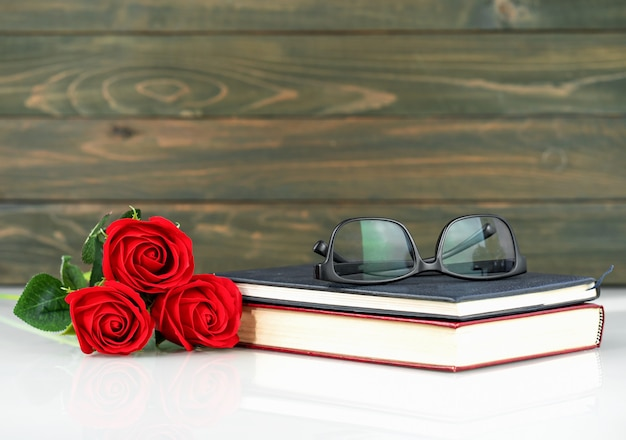 Red roses on table and book with copy space, valentine's day background with red roses