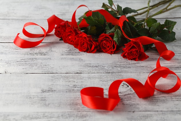 Red roses on table with ribbon