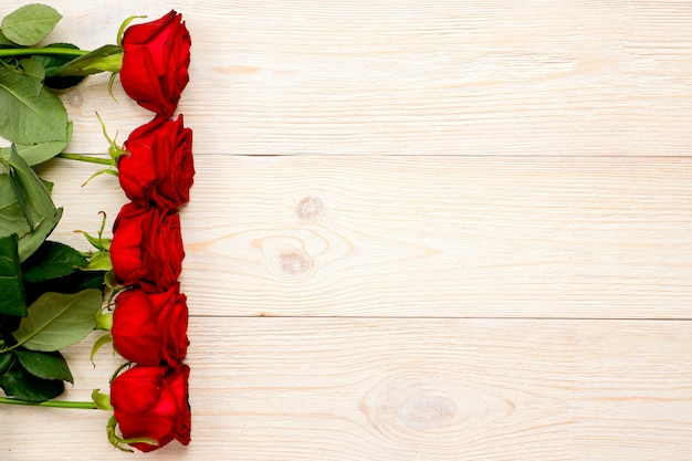 Red roses in vertical row on white desk, valentine's day post card