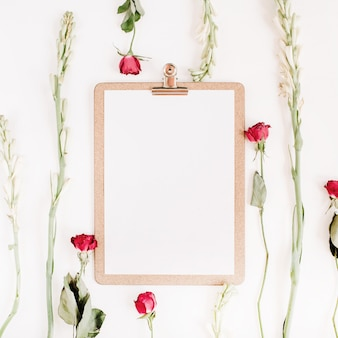 Red roses and white flowers frame with clipboard on white surface