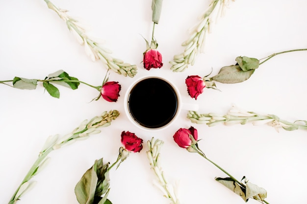 Red roses and white flowers frame with coffee mug on white surface