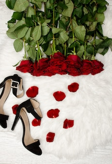 Red roses on white fur, black shoes and rose petals, top view