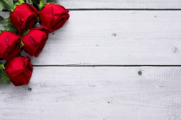 Red roses on white wood background with copy space for text for valentine and wedding frame concept.