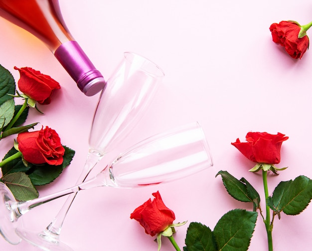 Red roses, wine and glasses for wine on a light pink