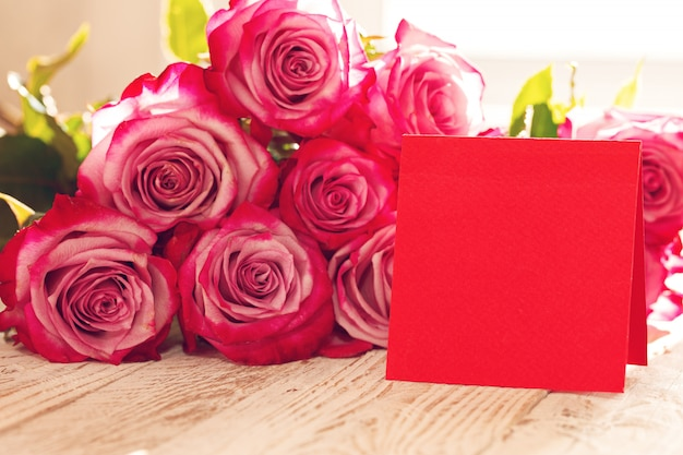 Red roses with blank red greeting card for valentines day