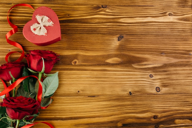 Red roses with box in heart shape on table
