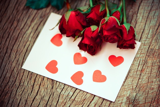 Red roses with card with hearts on wooden table