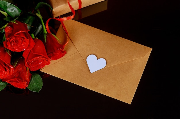黒いテーブルの上のグリーティングカードと赤いバラ。バレンタインデーのコンセプト。