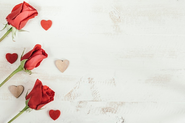 Red roses with hearts and white copy space