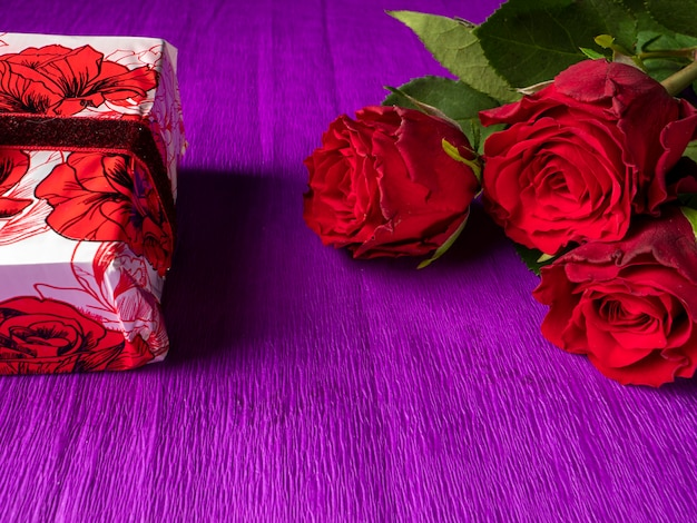 Red roses with red gift on purple