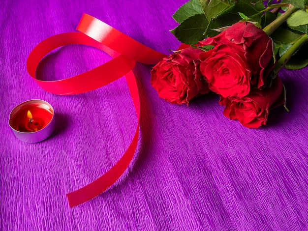 Red roses with ribbon and burning candle on purple
