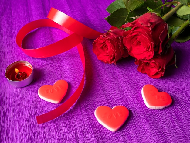 Red roses with ribbon, hearts and burning candle on purple