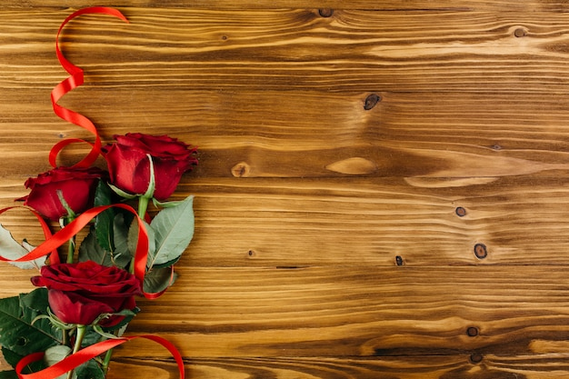 Red roses with ribbon on table