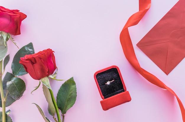 テーブル上のボックスに結婚指輪と赤いバラ