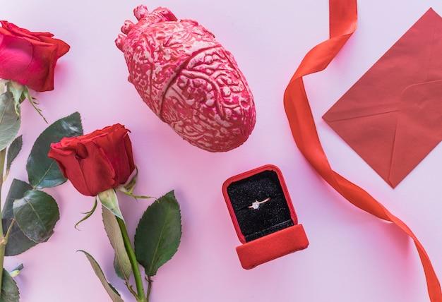 テーブルに結婚指輪と赤いバラ