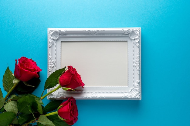 Red roses with white frame on blue background.