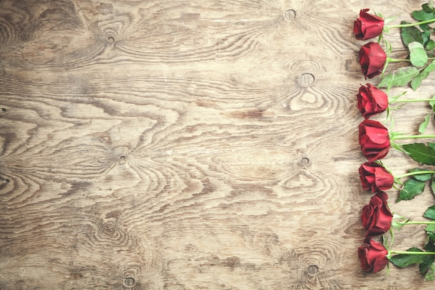 Red roses on wooden background.
