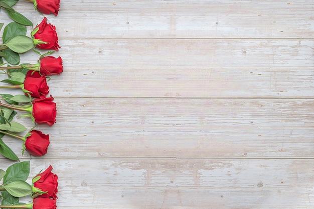Красные розы на деревянной поверхности макет для открытки приглашения на день святого валентина 14 февраля