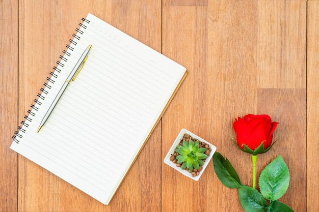 Red roses on wooden table and notepad