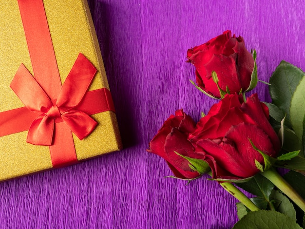 Red roses and yellow gift with red ribbon on purple