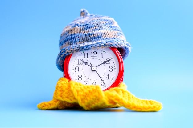 Красный круглый будильник в вязаной шерстяной синей шапке и желтом шарфе