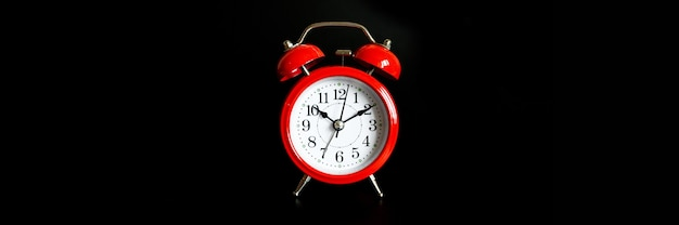 Red round analog alarm clock isolated on black background. time 10:10. banner