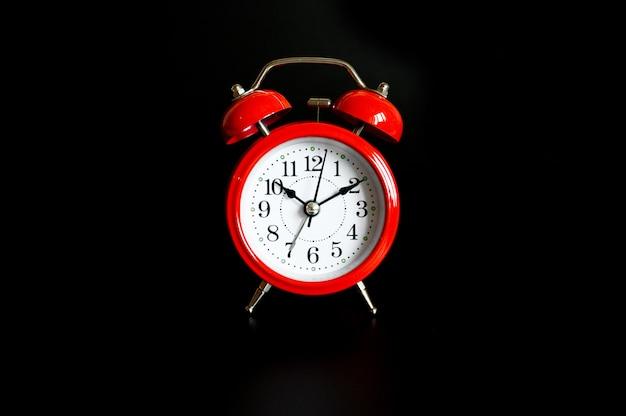 Red round analog alarm clock isolated on black background.