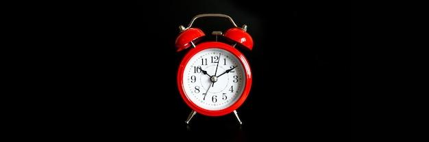 Красный круглый аналоговый будильник, изолированные на черном фоне. время 10:10. знамя