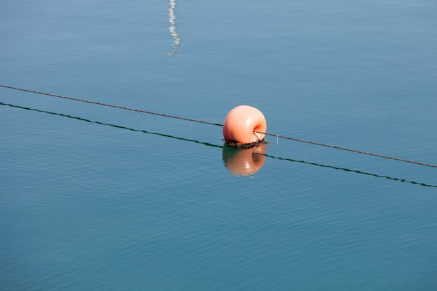 Red round buoy in the sea