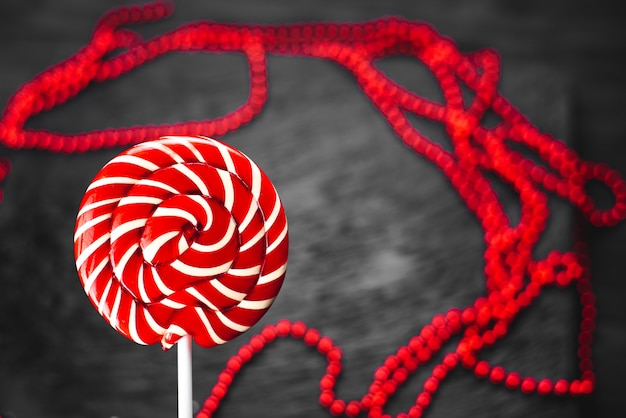 Red, round colored lollipop on black background sweet