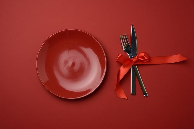 Красная круглая пустая керамическая тарелка, металлическая вилка и нож, перевязанные красной шелковой лентой, красный фон, вид сверху