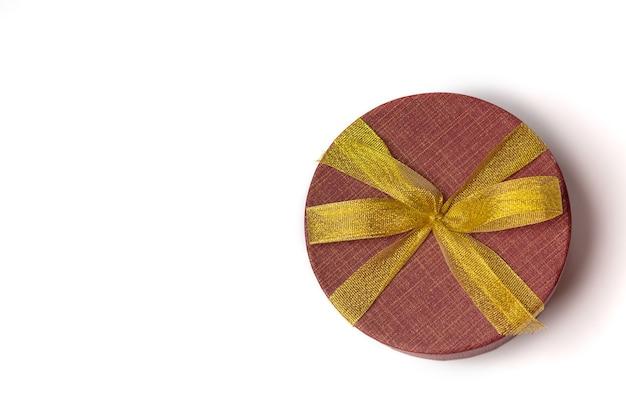 白い背景の上に弓と金色のリボンが付いた赤い丸いギフトボックス。テキスト用のスペース