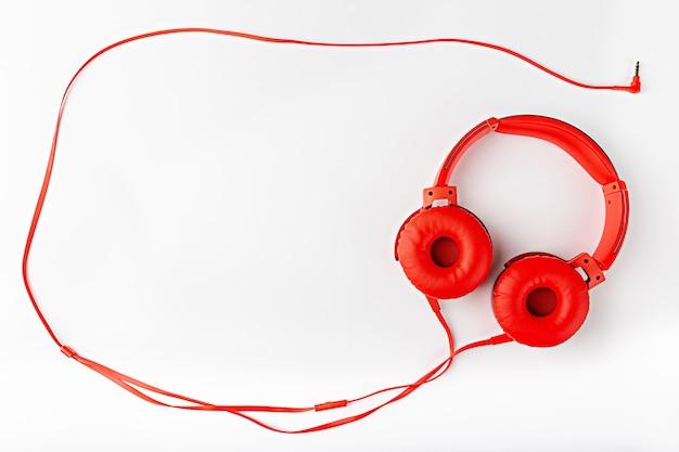 Красные круглые наушники со шнуром, образующим квартиру рамки, лежали на белом фоне с копией пространства.