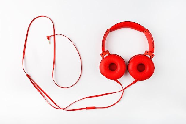 Красные круглые наушники со шнуром, образующим плоскую рамку, лежат на белом фоне с копией пространства
