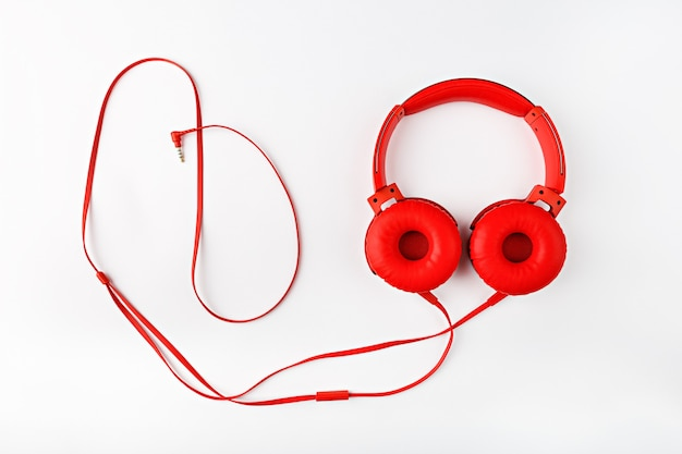 Red round headphones with cord forming frame flat lay on white background with copy space