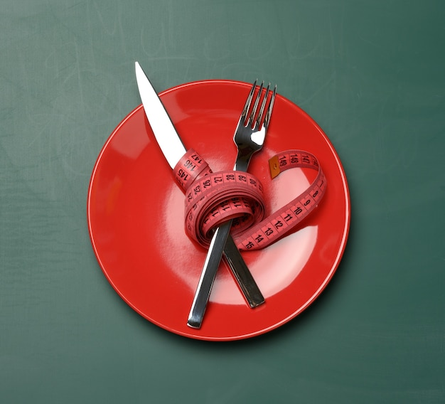 Red round plate and fork and knife wrapped in green measuring tape on a green background, weight loss concept, flat lay