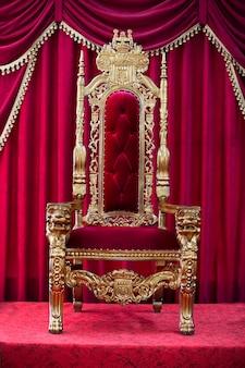 빨간 커튼의 배경에 빨간 왕실 의자. 왕을 위한 장소. 왕좌