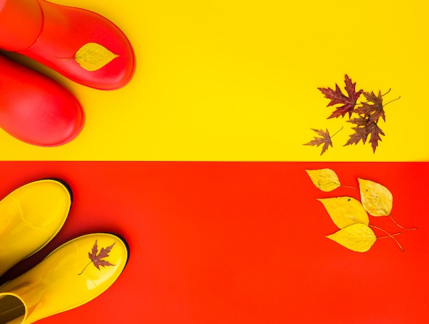 Red rubber boots stand on yellow and the yellow boots are on red.