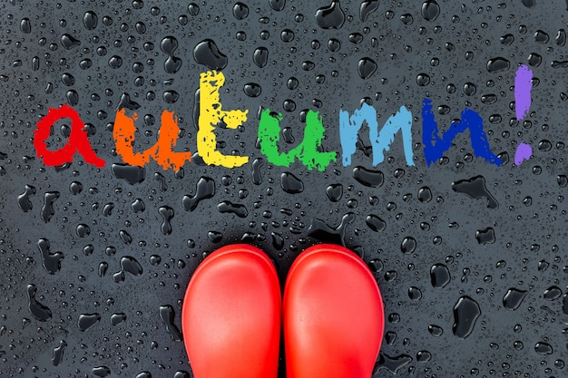 Red rubber boots on a  wet surface covered with raindrops and rainbow word