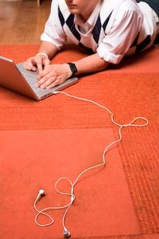 Red rug, laptop, white headphones