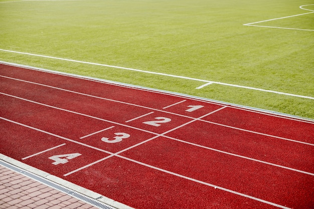 Red running track in stadium with numbers