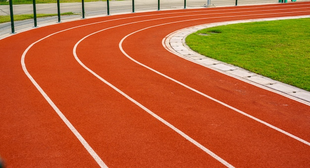 Red running track with white lines in outdoor sport stadium, side is a field and park.