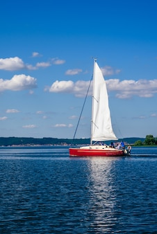Red sailing boat on the river at sunny day.