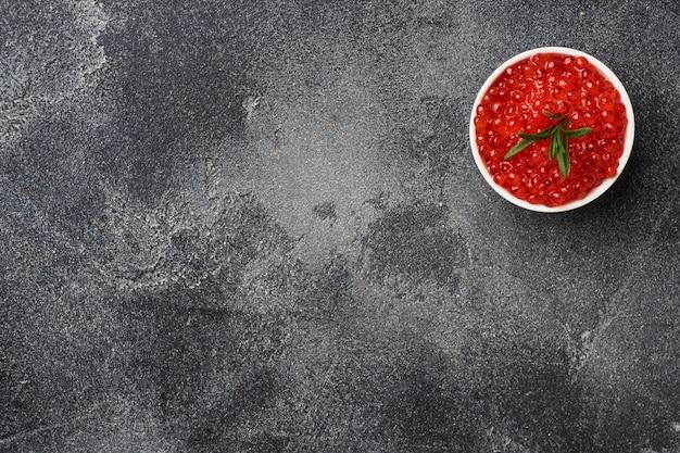 Red salmon caviar in a plate on a dark concrete. copy space. snack delicacy.