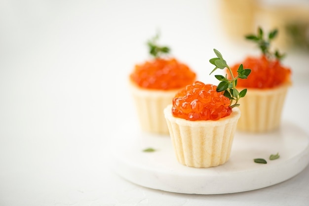 Red salted salmon caviar in tartlets decorated with thyme sprigs, close-up