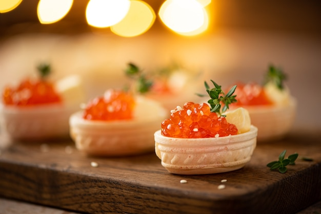 Red salted salmon caviar in waffle tartlets on a wooden board, close up