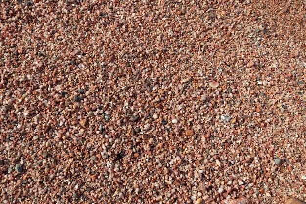 赤い砂と赤い海の海岸、自然なテクスチャ背景の石