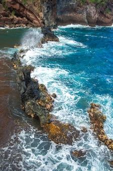 Red sand beach, maui in in hawaiian. ocean waves and rock.