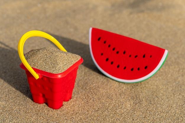 砂の上のスイカのおもちゃで赤い砂の城のバケツ