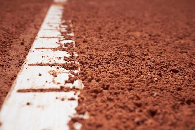 흰색 선 가까이 배경으로 붉은 모래 테니스 필드